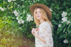 有淡紫色花的白肤金发的妇女在春天 库存图片