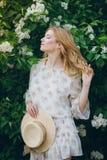有淡紫色花的白肤金发的妇女在春天 免版税库存图片