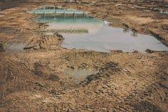 有深刻的水坑和大厦反射的泥泞和石渣路 图库摄影
