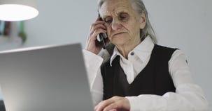 有深皱痕的一个老妇人在一个手机谈话,当坐在膝上型计算机时 影视素材