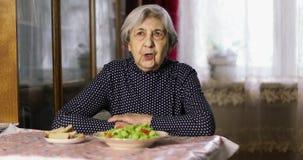 有深皱痕的一个老妇人坐在桌等待的午餐 股票视频