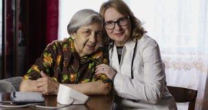 有深皱痕的一名老资深妇女和对照相机和微笑的年长医生神色 股票视频