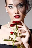 有深红玫瑰的美丽的妇女在面纱减速火箭的魅力开花 库存图片