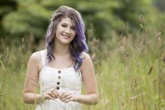 有深色和紫色头发的少妇在一个绿色公园 图库摄影