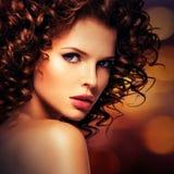 有深色的卷发的美丽的性感的妇女 图库摄影