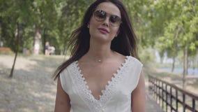 有深色的头发佩带的太阳镜和长的白色夏天时尚礼服的画象可爱的少女走沿a的 股票视频