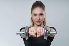 有深色的头发的年轻美丽的性感的妇女在有金属哑铃的一件黑T恤杉,画象健身体育照片 免版税库存图片