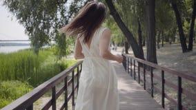 有深色的运行在一个木桥的头发佩带的太阳镜和长的白色夏天时尚礼服的可爱的少女 影视素材