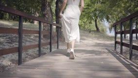 有深色的运行在木的头发佩带的太阳镜和长的白色夏天时尚礼服的画象逗人喜爱的少女 影视素材
