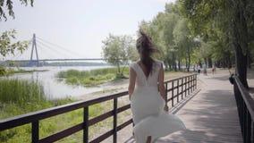 有深色的运行在a的头发佩带的太阳镜和长的白色夏天时尚礼服的画象迷人的少女 影视素材