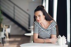 有深色的头发的可爱的妇女,性感的微笑的女孩户内,在咖啡馆,弄脏了背景 她有可爱的微笑 免版税图库摄影