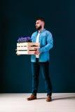 有深色的头发的年轻可爱的有胡子的行家人,穿戴在蓝色牛仔布衬衣,站立户内,拿着木箱 库存照片