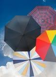 有深蓝天空的四把不同开放伞 图库摄影