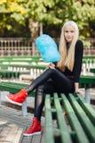 有深蓝蓝色棉花糖开会的年轻时髦的运动的白肤金发的美丽的青少年的女孩盘腿在公园长椅在一温暖的秋天天a 免版税库存照片