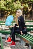 有深蓝蓝色棉花糖开会的年轻时髦的运动的白肤金发的美丽的青少年的女孩盘腿在公园长椅在一温暖的秋天天a 免版税库存图片