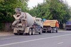 有混凝土搅拌机的卡车在沿路线的沥青站立 免版税图库摄影