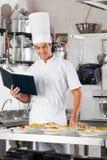 有清单和面团盘的厨师在柜台 图库摄影