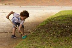 年轻从车道的男孩清扫的叶子 免版税库存图片