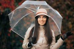 有清楚的塑料透明伞的愉快的妇女在秋天雨中 免版税库存照片