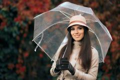 有清楚的塑料透明伞的愉快的妇女在秋天雨中 免版税库存图片
