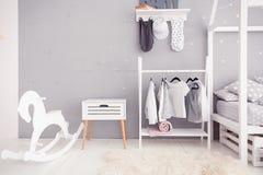 有清楚的墙壁、玩具和木马的空的托儿所室 图库摄影