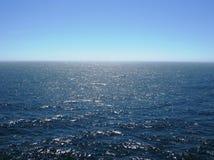 有清楚的天际的,明媚的阳光,在浪潮起伏的水的反射太平洋 免版税图库摄影