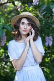 有清楚的皮肤和波浪棕色头发的一个女孩在一个草帽在绽放的一个淡紫色庭院里 美丽的镇静女孩画象 过敏,sprin 库存图片