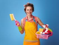 有清洁物品和刷子篮子的主妇在蓝色 库存图片