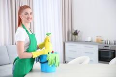 有清洁物品的年轻女工在厨房里 免版税库存图片