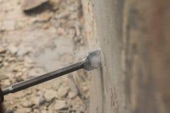 有清洗红砖墙壁的电子锤子的工作者 免版税图库摄影