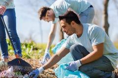 有清洗公园区域的垃圾袋的志愿者 免版税图库摄影
