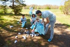 有清洗公园区域的垃圾袋的志愿者 免版税库存图片