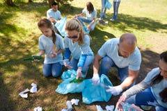 有清洗公园区域的垃圾袋的志愿者 免版税库存照片