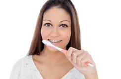 有清洗她的牙的托架的可爱的少妇 免版税图库摄影