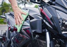 有清洁摩托车的手 图库摄影