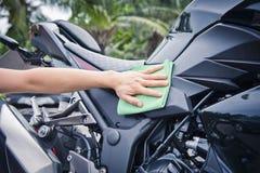 有清洁摩托车的手 免版税库存图片