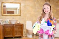 有清洁物品的年轻主妇在卫生间里 免版税库存照片