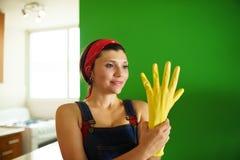 有清洗黄色乳汁的手套的年轻西班牙妇女在家 库存图片