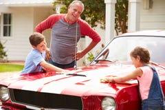 有清洗被恢复的经典汽车的孙的祖父 免版税库存照片