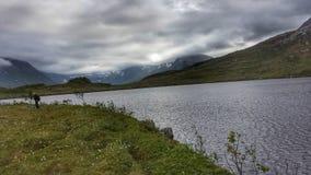有渔夫的美丽的夏天山渔湖后面的 免版税库存照片