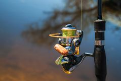 有渔夫的转动和卷轴的钓鱼竿 免版税库存图片
