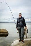 有渔战利品的愉快的钓鱼者 库存图片