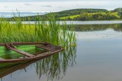有渔船和反射的一个镇静平安的湖 库存图片