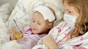 有温度的病的女孩 孩子以热病在与她的母亲的床上在,吃果子并且使用膝上型计算机 影视素材
