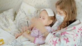 有温度的病的女孩 孩子以热病在与她的母亲的床上在,吃果子并且使用膝上型计算机 股票录像