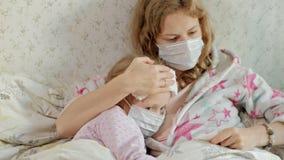 有温度的病的女孩 孩子以热病在与她的母亲的床上在,吃果子并且使用膝上型计算机 股票视频