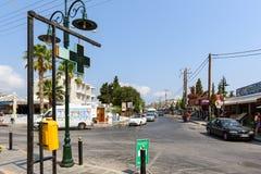 有温度计的中央交叉路,显示热天气温度,在药房签到Faliraki镇 Lindos 库存图片