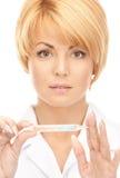 有温度计的可爱的女性医生 库存图片