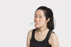 有温度计的妇女在遭受麻疹的嘴 免版税图库摄影