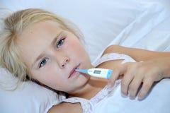 有温度计的病的女孩在说谎在床上的嘴 库存照片